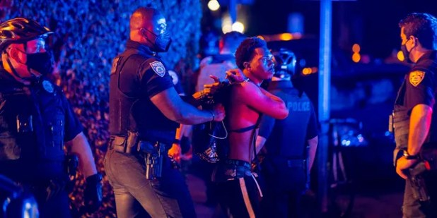A man is arrested while away a few hours after curfew in Miami Beach, Florida, on Sunday, March 21, 2021. Miami Beach commissioners voted unanimously Sunday to extend the curfew from 8 p.m. to 6 p.m. am Thursday through Sunday in the South Beach entertainment district.  until at least April 12, effectively closing a spring break hot spot in one of the few fully open states during the pandemic.  (Daniel A. Varela / Miami Herald via AP)