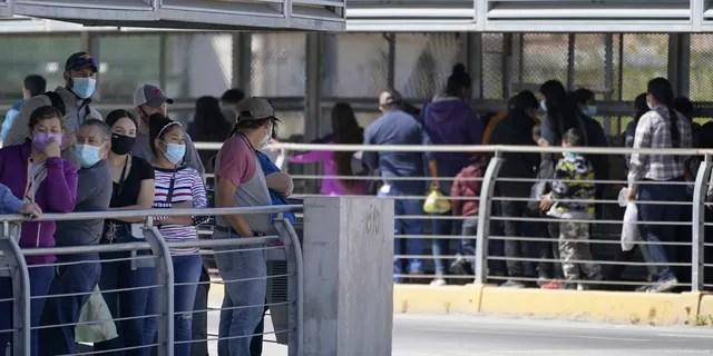 Travelers, left, waiting in line to cross a customs area into the United States at the McAllen-Hidalgo International Bridge look on as a group of migrants, right, are deported to Reynosa, Mexico. (AP Photo/Julio Cortez)