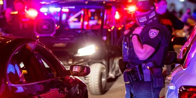 Miami Beach Police arrive at the scene to disperse a crowd that formed near Seventh Street and Alton Road after crowds were evicted from Ocean Drive in Miami Beach, Fla., On Sunday.  (AP / Miami Herald)
