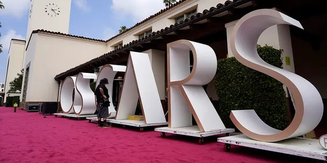 An Academy Awards crew member looks over a background element for the red carpet at Union Station, one of the locations for Sunday's 93rd Academy Awards, Saturday, April 24, 2021, in Los Angeles.