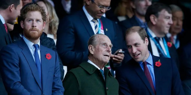 In this Oct. 31, 2015 file photo Britain's Prince Harry, left, and his brother Prince William, right, stand with their grandfather the Duke of Edinburgh as they wait for the start of the Rugby World Cup final between New Zealand and Australia at Twickenham Stadium, London. Philip's grandson Prince Harry, who stepped away from royal duties last year and now lives in California, will attend the service along with other members of the royal family, palace officials have said.. His wife, Meghan, Duchess of Sussex, is pregnant and has been advised by her doctor not to make the journey.