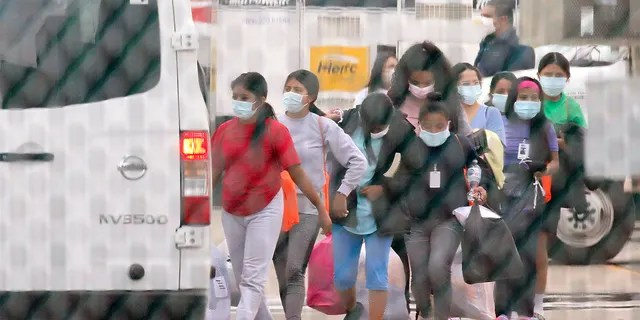 Teenage migrant girls are loaded into vans to be transported out of the National Association of Christian Churches facility, on Saturday, April 17, 2021, in Houston. (Godofredo A. Vásquez/Houston Chronicle via AP)
