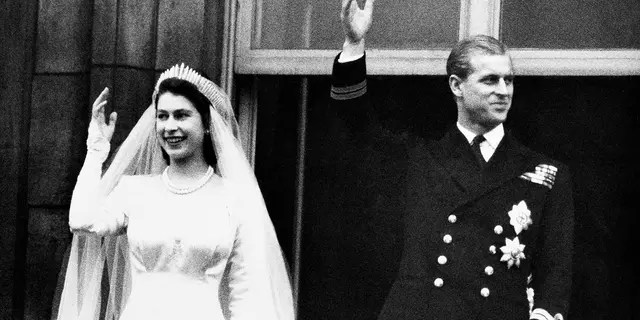 In this Nov. 20, 1947 file photo, Britain's Princess Elizabeth and her husband the Duke of Edinburgh wave to the crowds on their wedding day, from the balcony of Buckingham Palace in London. Buckingham Palace officials announced on Friday that the husband of Queen Elizabeth II died at Windsor Castle.
