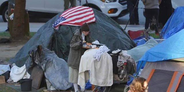 In this March 24, 2021, file photo a woman eats at her tent at the Echo Park homeless encampment at Echo Park Lake in Los Angeles. (AP Photo/Damian Dovarganes)