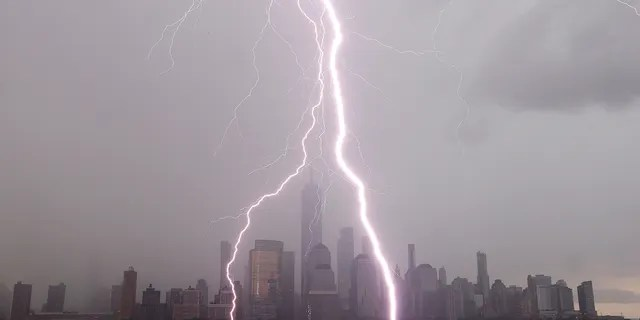 Jersey City, New Jersey - JULY 6: Two lightning bolts frame One World Trade Center as they hit the Hudson River in front of the skyline of lower Manhattan in New York City during a thunderstorm on July 6, 2020 as seen from Jersey City, New Jersey. (Photo by Gary Hershorn/Getty Images)