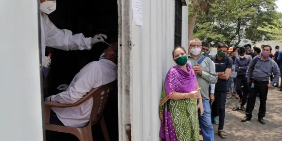 May 6, 2021: In this file photo, a health worker takes a nasal swab sample of a person to test for COVID-19 as others wait for their turn outside a field hospital in Mumbai, India.