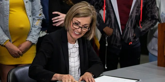 Iowa Gov. Kim Reynolds signs a bill into law expanding Iowa's charter school program, on Wednesday, May 19, 2021, in Des Moines. (Reuters)