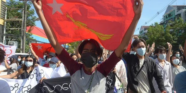 Anti-coup protesters display a party flag of the National League for Democracy (NLD) during a demonstration in Yangon, Burma, Friday, May 14, 2021. (AP Photo)