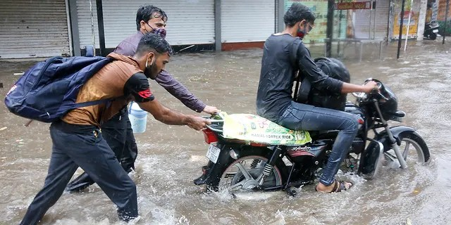 Two men help a motorist to wade through a waterlogged street after heavy rains in Ahmedabad, India, Tuesday, May 18, 2021. Cyclone Tauktae, the most powerful storm to hit the region in more than two decades, packed sustained winds of up to 210 kilometers (130 miles) per hour when it came ashore in Gujarat state late Monday. (AP Photo/Ajit Solanki)