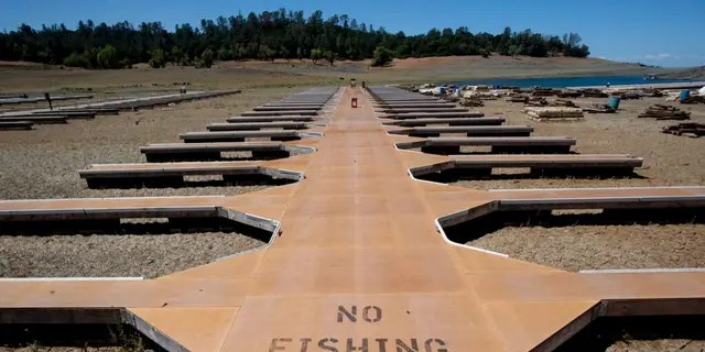 Empty boat docks sit on dry land at the Browns Ravine Cove area of drought-stricken Folsom Lake in Folsom, California, Saturday, May 22, 2021. (Associated Press)