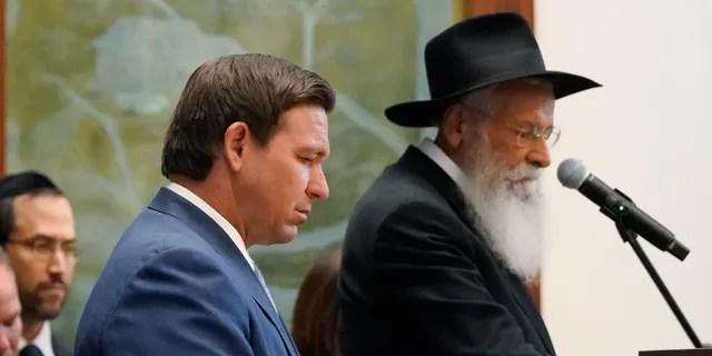 Florida Gov. Ron DeSantis, left, and Rabbi Sholom Lipskar participate in a moment of silence, Monday, June 14, 2021, at the Shul of Bal Harbour, a Jewish community center in Surfside, Fla. (AP Photo/Wilfredo Lee)