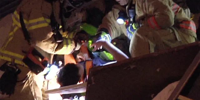 This photo taken from video provided by ReliableNewsMedia, a firefighter fist bumps a survivor, after being pulled from the rubble of the Champlain Towers South Condo after the multistory building partially collapsed in Surfside, Fla., early Thursday. (ReliableNewsMedia via AP)