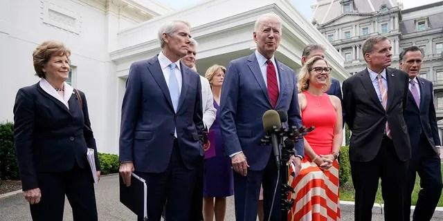 President Joe Biden, with a bipartisan group of senators, speaks Thursday June 24, 2021, outside the White House in Washington. Biden invited members of the group of 21 Republican and Democratic senators to discuss the infrastructure plan. From left are, Sen. Jeanne Shaheen, D-N.H., Sen. Rob Portman, R-Ohio, Sen. Bill Cassidy, R-La., Sen. Lisa Murkowski, R-Alaska, Biden, Sen, Joe Manchin, D-W.Va., Sen. Kyrsten Sinema, D-Ariz, Sen. Mark Warner, D-Va., and Sen. Mitt Romney, R-Utah. (AP Photo/Jacquelyn Martin)