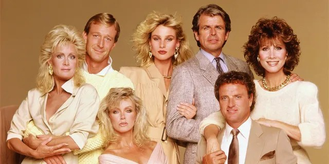 Studio portrait of the cast of the American nighttime soap opera series 'Knots Landing,' 1991. From left: Actors Joan van Ark, Ted Shackelford, Donna Mills (seated), Nicollette Sheridan, William Devane, Kevin Dobson, and Michele Lee.