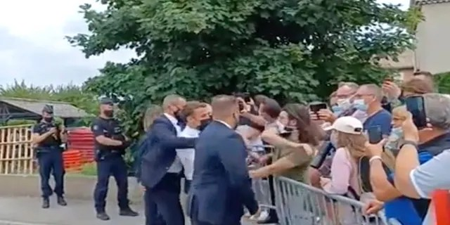 In this image taken from video, French President Emmanuel Macron, center, is slapped by Damien Tarel -- who is in a green T-shirt -- during a visit to Tain-l'Hermitage in France on Tuesday. (BFM TV via AP)