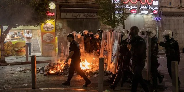 Angry demonstrators set fires, block the streets of the city center and clash with riot police following the death of Nizar Banat, an outspoken critic of the Palestinian Authority, in the West Bank city of Ramallah, on Thursday. (AP)