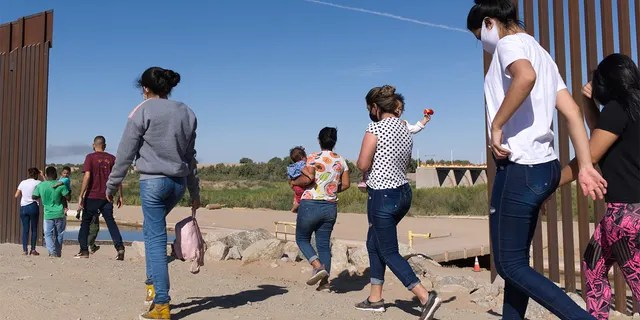 In this Tuesday, June 8, 2021, photo, a group of Brazilian migrants make their way around a gap in the U.S.-Mexico border in Yuma, Ariz., seeking asylum in the United States after crossing over from Mexico. (AP Photo/Eugene Garcia)