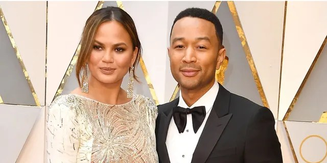 John Legend told TMZ cameras on Tuesday that his wife is 'doing great' amid the cyberbullying scandal.
