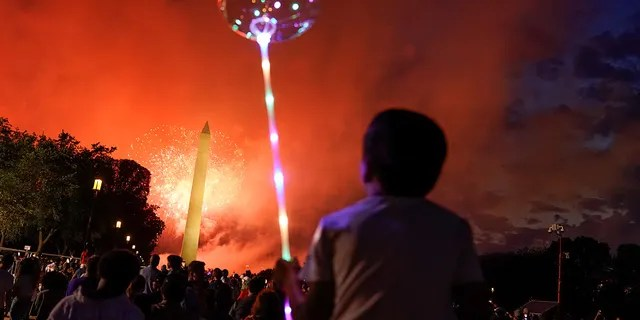 People enjoy the fireworks as they gather for the annual Independence Day celebration at the National Mall in Washington, U.S., July 4, 2021. (REUTERS)