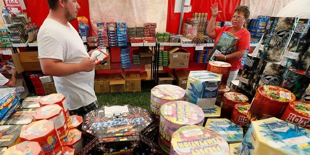 FILE - In this Thursday, June 15, 2017, file photo, Bryce Walter, of Ankeny, Iowa, talks with customer Deb Crowl, right, about fireworks for sale in a tent owned by the Iowa Fireworks Company, in Adel, Iowa. (AP Photo/Charlie Neibergall, File)