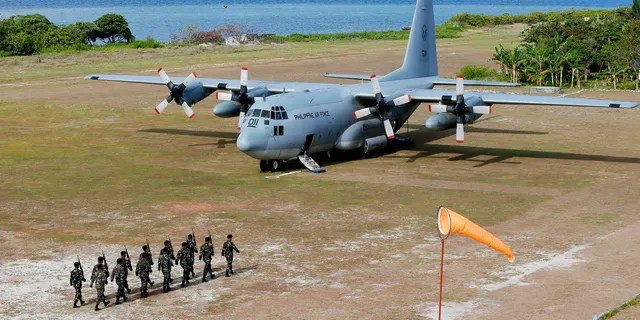 FILE - This April 21, 2017, file photo shows a Philippine Air Force C-130 transport plane as Philippine troops march at the Philippine-claimed Thitu Island off the disputed Spratlys chain of islands in the South China Sea in western Philippines. The Philippine military chief said Sunday, July 4, 2021, a C-130 plane carrying troops has crashed in the country's south after missing the runway and multiple people have been rescued. (AP Photo/Bullit Marquez, File)