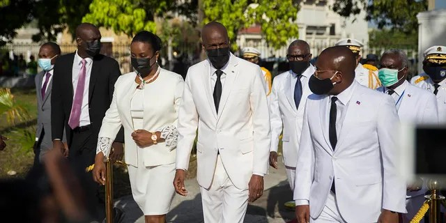 Haitian President Jovenel Moise, center, walks with first lady Martine Moise, left, and interim Prime Minister Claude Joseph, right, during a ceremony marking the 218th anniversary of the creation of the Haitian flag in Port-au-Prince, Haiti on May 18, 2021. (AP Photo/Joseph Odelyn, File)