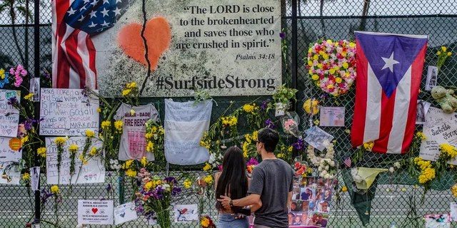 Momentos, personal items and flowers are seen displayed at the Surfside Wall of Hope & Memorial on Wednesday, July 7, 2021, in Surfside, Fla. The display honors those who died during the collapse of the 12-story oceanfront condo, Champlain Towers South in Surfside (Al Diaz/Miami Herald via AP)