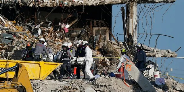 Search and rescue personnel remove remains on a stretcher as they work atop the rubble at the Champlain Towers South condo building where scores of people remain missing more than a week after it partially collapsed, Friday, July 2, 2021, in Surfside, Florida.