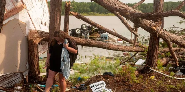 This photo provided by the U.S. Navy, Missy Lattanzie, an RV park resident, searches through her belongings that were destroyed after a tornado touched down Wednesday on Naval Submarine Base Kings Bay, on Thursday, July 8, 2021 in Kings Bay, Ga. Severe weather from Tropical Storm Elsa spurred tornado warnings in Delaware and New Jersey early Friday as the system moved over the mid-Atlantic states and into the northeastern United States. (Mass Communication 3rd Class Aaron Xavier Saldana/U.S. Navy via AP)