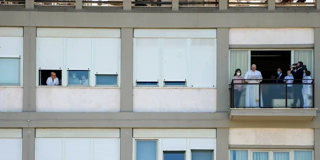 Pope Francis appears on a balcony of the Agostino Gemelli Polyclinic in Rome, Sunday, July 11, 2021, where he is recovering from intestinal surgery, for the traditional Sunday blessing and Angelus prayer. Pope Francis is 84 and had a part of his colon removed a week ago. (AP Photo/Alessandra Tarantino)