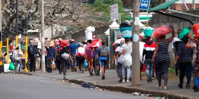 People make their way from a shopping mall carrying goods in Durban, South Africa, Tuesday July 13, 2021, as ongoing looting and violence continues.