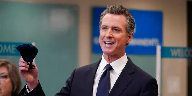 Gov. Gavin Newsom holds a face mask while speaking at a news conference in Oakland, Calif., Monday, July 26, 2021. (AP Photo/Jeff Chiu)
