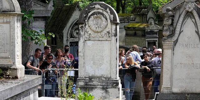 Fans gather at the tomb of rock singer Jim Morrison at the Pere-Lachaise cemetery in Paris, Saturday, July 3, 2021. (Associated Press)