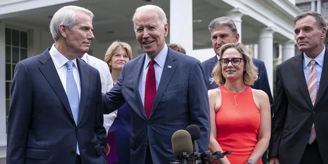 FILE – President Joe Biden, center, addresses Senator Rob Portman, a Republican from Ohio, left, while speaking to members of the media with Senator Mark Warner, a Democrat from Virginia, from right, Senator Kyrsten Sinema, a Democrat from Arizona, Senator Joe Manchin, a Democrat from West Virginia, and Senator Lisa Murkowski, a Republican from Alaska, outside the West Wing of the White House following a meeting in Washington, D.C., U.S., on Thursday, June 24, 2021.