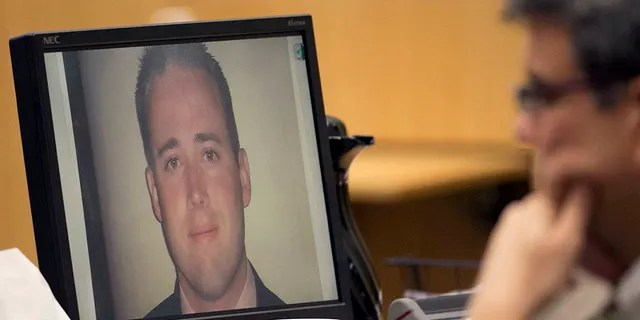 A photograph of Travis Alexander appears on a computer monitor in front of defense attorney Kirk Nurmi as Alexander's family speaks to the jury during the sentencing phase retrial of Jodi Arias at Maricopa County Superior Court in Phoenix on Thursday, Oct. 30, 2014. Arias was found guilty of first-degree murder.