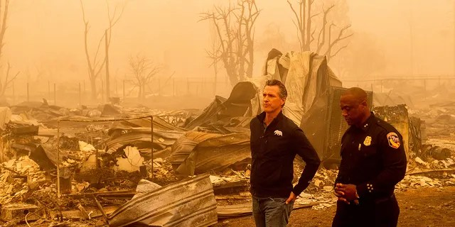 California Gov. Gavin Newsom surveys Greenville homes leveled by the Dixie Fire on Saturday, Aug. 7, 2021, in Plumas County, California. Accompanying him is Cal Fire Assistant Region Chief Curtis Brown. (Associated Press)
