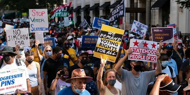 Demonstrators hold signs during a march for voting rights, marking the 58th anniversary of the March on Washington, Saturday, Aug. 28, 2021, in Washington. (AP Photo/Jose Luis Magana)