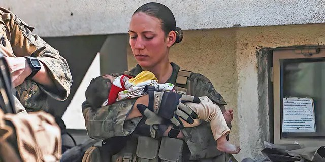 In this Aug. 20, 2021, image provided by the U.S. Marine Corps, Marines assigned to the 24th Marine Expeditionary Unit (MEU), including Sgt. Nicole Gee calms an infant during an evacuation at Hamid Karzai International Airport in Kabul, Afghanistan. Officials said Aug. 28, that Gee of Sacramento, Calif., was one of the Marines killed in Thursday's bombing at the airport.