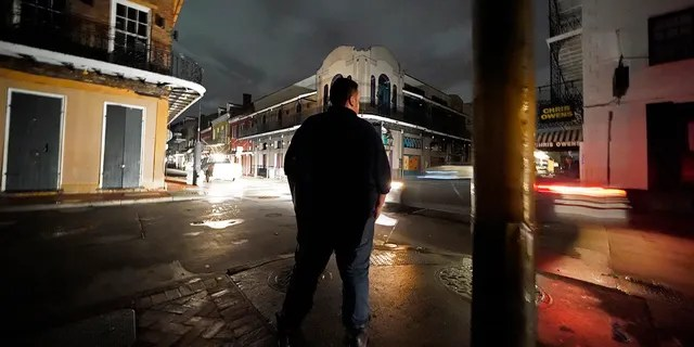 Greg Nazarko, manager of the Bourbon Bandstand bar on Bourbon Street, stands outside the club, where he rode out the storm, after Hurricane Ida that knocked out power in New Orleans, Monday, Aug. 30, 2021. (AP Photo/Gerald Herbert)
