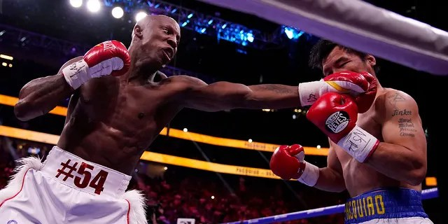 Manny Pacquiao, right, of the Philippines, is hit by Yordenis Ugas, of Cuba, in a welterweight championship boxing match Saturday, Aug. 21, 2021, in Las Vegas. (AP Photo/John Locher)
