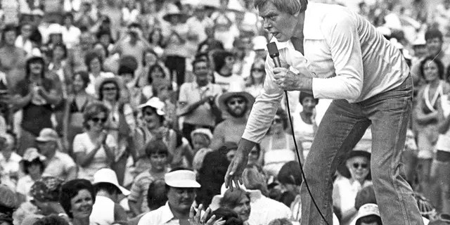 Tom T. Hall leans to the edge of the stage at the 1977 Jamboree in the Hills to meet the people near St. Clairsville, Ohio. (Associated Press)