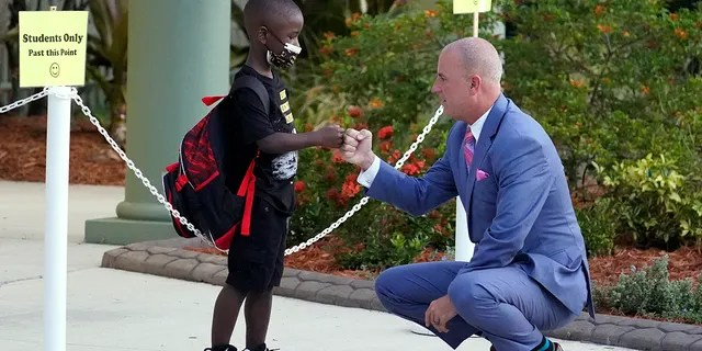 Addison Davis, Hillsborough County Superintendent of Schools, right, fist bumps student James Braden before he heads to class on the first day of school at Sessums Elementary School Tuesday, Aug. 10, 2021, in Riverview, Florida. Students are required to wear protective masks while in class unless their parents opt out.