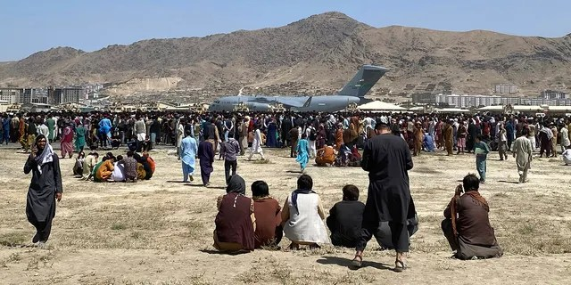 Hundreds of people gather near a U.S. Air Force C-17 transport plane at a perimeter at the international airport in Kabul, Afghanistan, on Monday. (Associated Press)