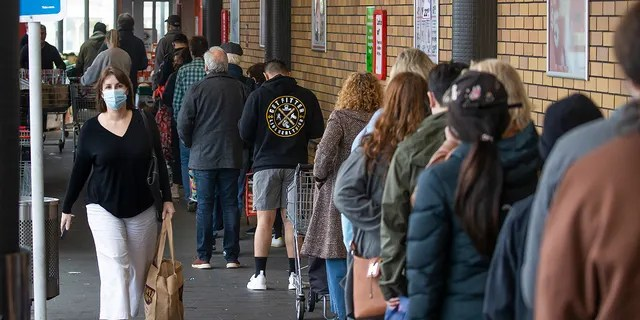 Shoppers lineup to enter a supermarket in Auckland, New Zealand, Tuesday, Aug. 17, 2021. New Zealand's government took drastic action Tuesday by putting the entire nation into a strict lockdown after detecting just a single community case of the coronavirus. (Brett Phibbs/New Zealand Herald via AP)