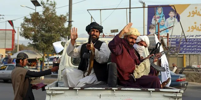 Taliban fighters wave from the back of a pickup truck, in Kabul, Afghanistan, Monday, Aug. 30, 2021. (AP Photo/Khwaja Tawfiq Sediqi)