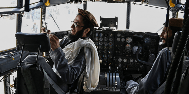 TOPSHOT - Taliban fighters sit in the cockpit of an Afghan Air Force aircraft at the airport in Kabul on August 31, 2021, after the US has pulled all its troops out of the country to end a brutal 20-year war -- one that started and ended with the hardline Islamist in power. (Photo by Wakil KOHSAR / AFP) (Photo by WAKIL KOHSAR/AFP via Getty Images)