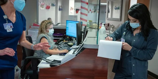 Healthcare worker and new employee Amber Blunk, right, signs up for her first COVID-19 vaccination at Nashville General Hospital Nashville Tenn. on Friday, Aug. 20, 2021.