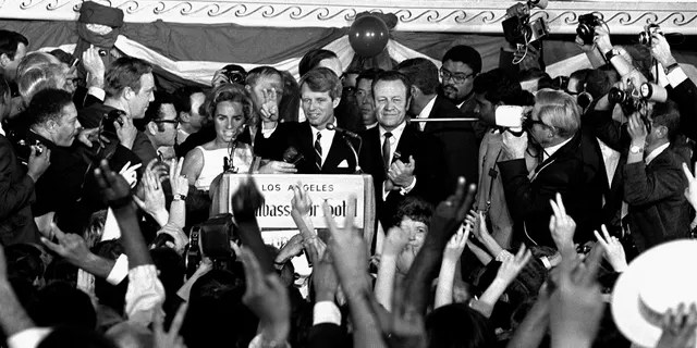In this June 5, 1968, file photo, Sen. Robert F. Kennedy addresses campaign workers moments before being shot in Los Angeles. At his side are his wife, Ethel, and his California campaign manager, Jesse Unruh, speaker of the California Assembly. (AP Photo/Dick Strobel, File)