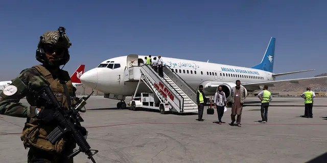 A Taliban soldier stands guard as passengers disembark on arrival from Kandahar, at Hamid Karzai International Airport in Kabul, Afghanistan, Sunday, Sept. 5, 2021. (AP Photo/Wali Sabawoon)