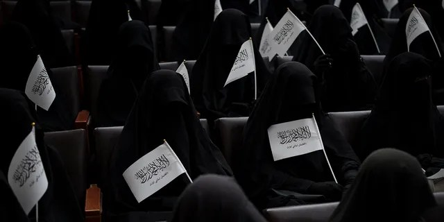Women wave Taliban flags as they sit inside an auditorium at Kabul University's education center during a demonstration in support of the Taliban government in Kabul, Afghanistan, Saturday, Sept. 11, 2021.